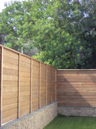 Mise en place d'une palissade en bois sur muret - Chevallier Paysage